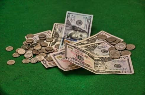 Fifty and hundred dollar bills and silver coins stacked on green felt