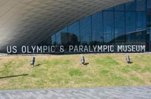 Large white letters spelling US Olympic and Paralympic Museum in front of building with large windows