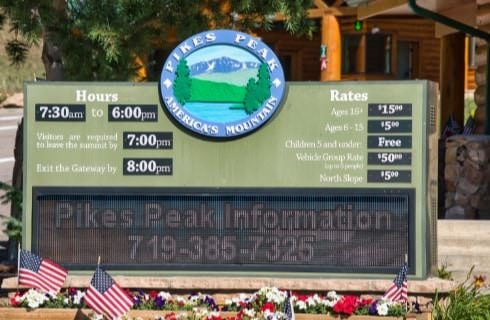 Welcome sign for Pikes Peak showing hours and rates information