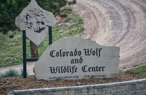 White stone sign with black lettering for Colorado Wolf and Wildlife Center