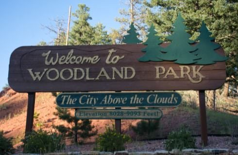 Large brown wooden sign with green pine trees saying Welcome to Woodland Park