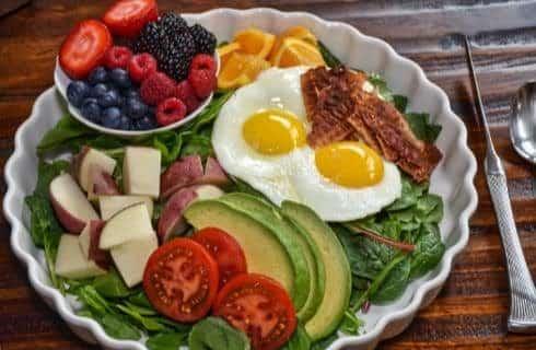 Breakfast dish full of fresh greens, sliced avocados and tomatoes, potatoes, overeasy eggs, bacon, strawberries, blueberries, raspberries, and blackberries
