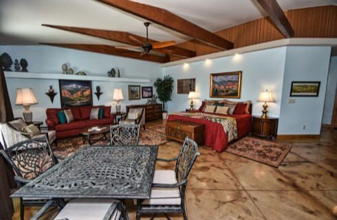 Large suite with bed, sitting area, dining area, and wooden beams in the ceiling