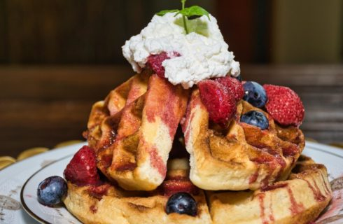 Close up view of waffles covered with strawberries, blueberries, whipped cream, and mint sprig on top