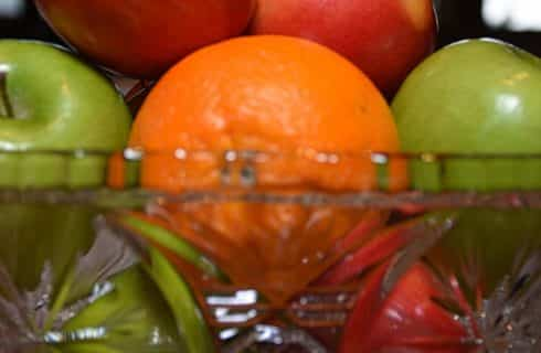 Close up view of red and green apples and oranges in decorative glass bowl