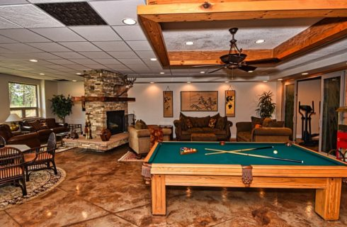 Large room with stamped concrete floor, multiple sofas and chairs, stone fireplace, wooden pool table, and a dining area