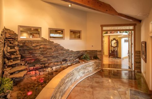 Entry inside of property with stamped concrete flooring and large stone brick water feature in the corner