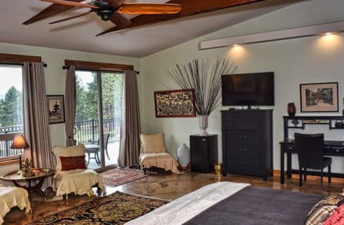 Large suite with black furniture, covered chairs, and patio door leading to balcony looking out to the mountains