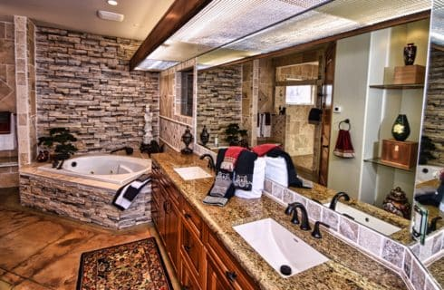 Large bedroom with stamped concrete flooring, stone bricked sunken tub area, large double vanity and tiled shower area