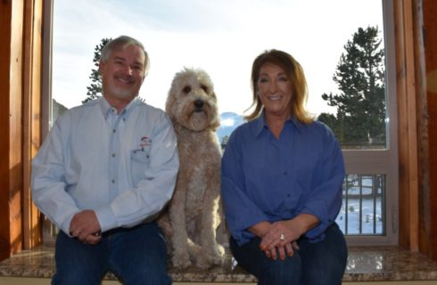 Man in light blue button up shirt, white fluffy dog, and woman in dark blue button up shirt sitting in front of a window all smiling at the camera
