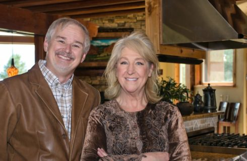 Man with brown leather jacket and woman with brown decorative shirt smiling at the camera