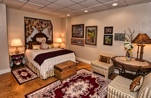 Bed room with large dark wooden headboard with neutral bedding, white, burgundy, and gold pillows, mop doll, end tables with lamps, and sitting area