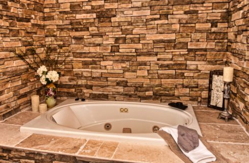 Sunken tub surrounded by tile and stone bricked wall