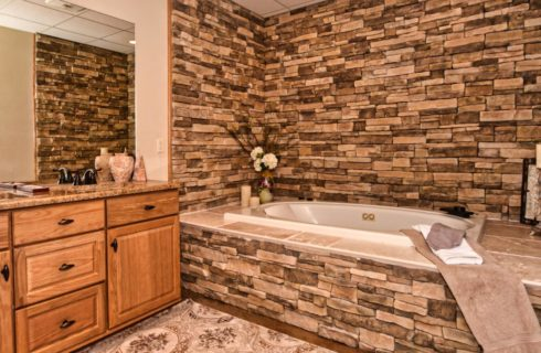 Bathroom with double vanity and sunken tub surrounded by tile and stone bricked wall