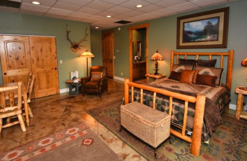 Large suite with knotty pine furniture, antler lamps, armchair, dining area, and view to the bathroom