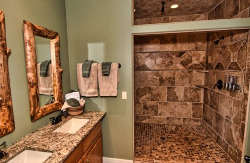 Large bathroom with knotty pine framed mirrors, double vanity and large walk in tiled shower