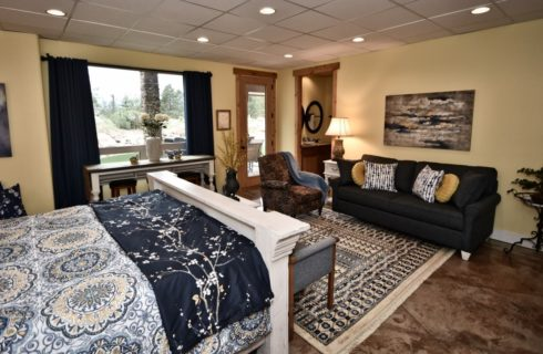 Large bedroom suite with light wooden distressed furniture, view to the bathroom, sitting area, and large window with a view to the outside