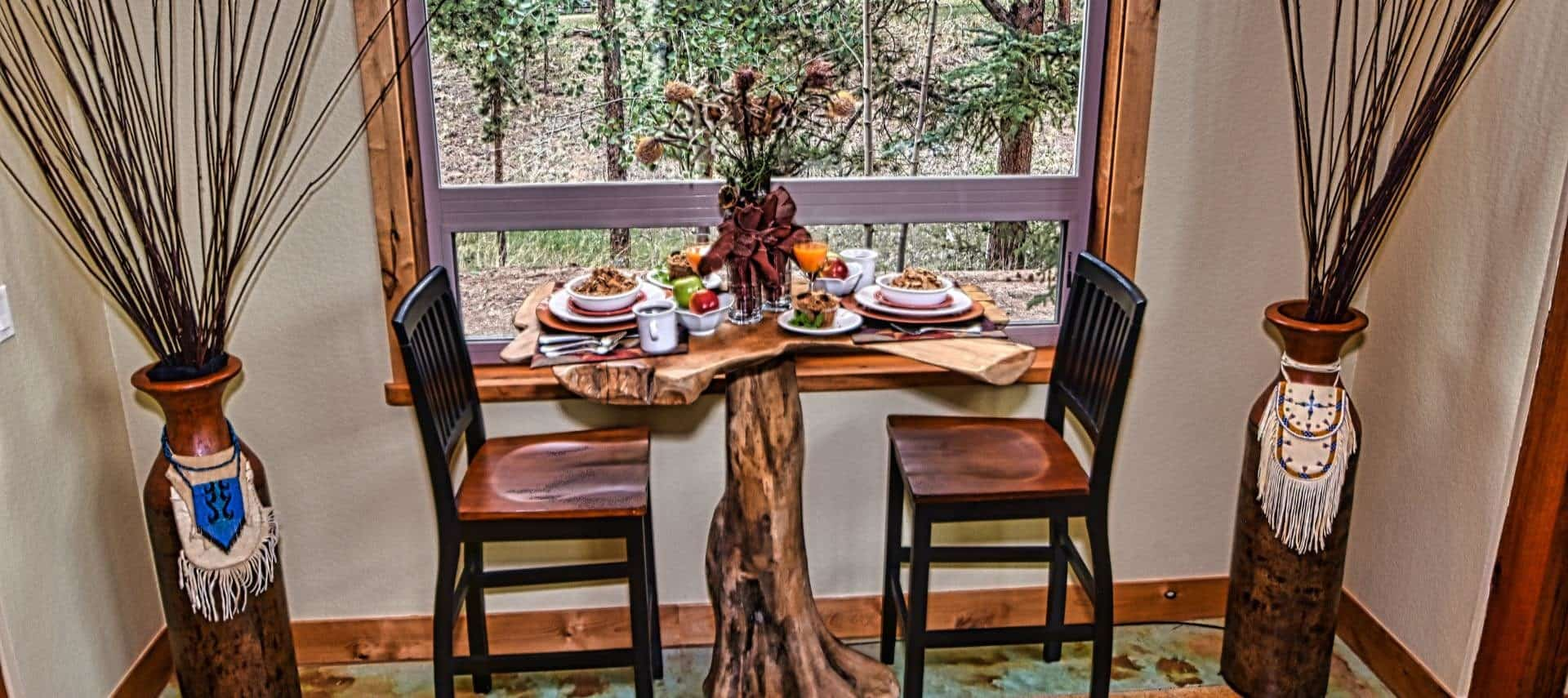 Two wooden chairs and a table made of reclaimed wood set with dishes full of breakfast items near large window with view to outside