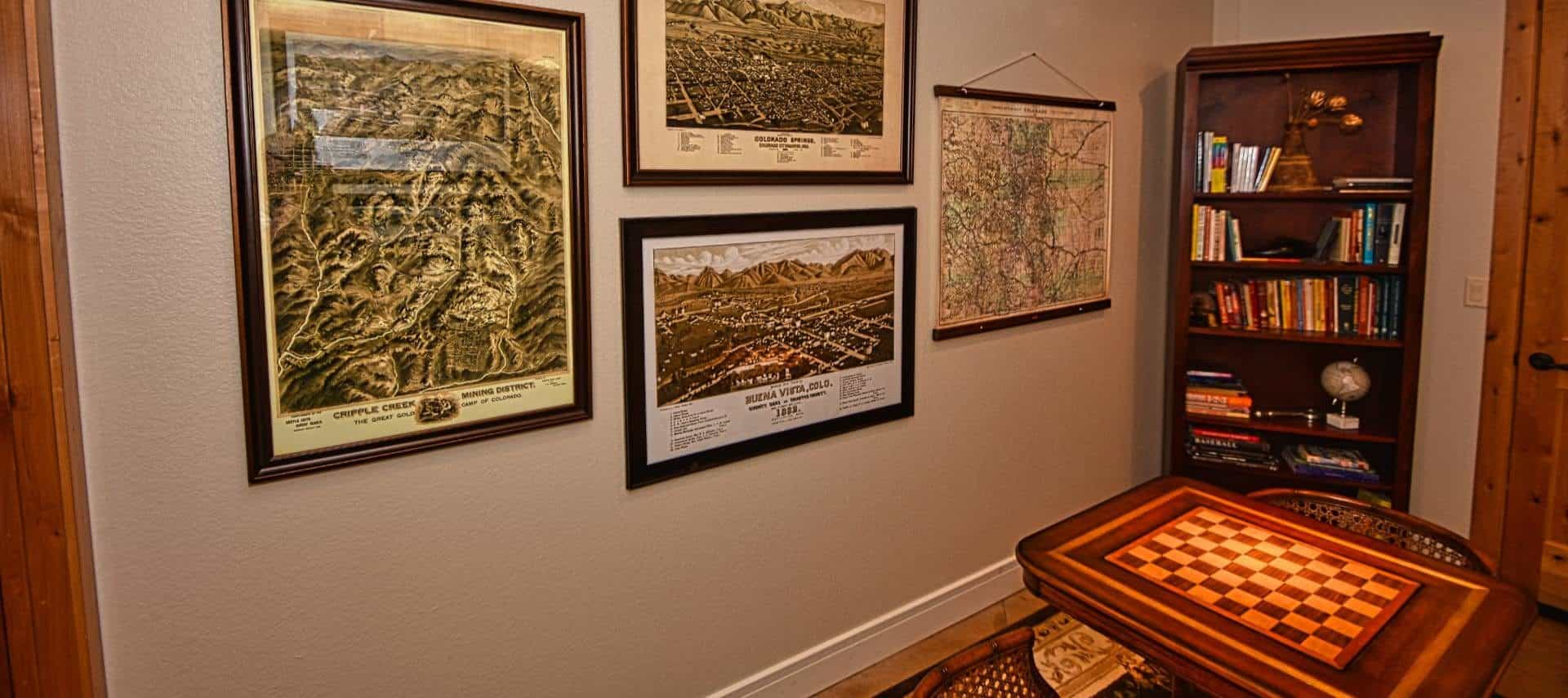 Room with wooden game board table with chairs, dark wooden bookcase with books and games, and framed pictures of town maps