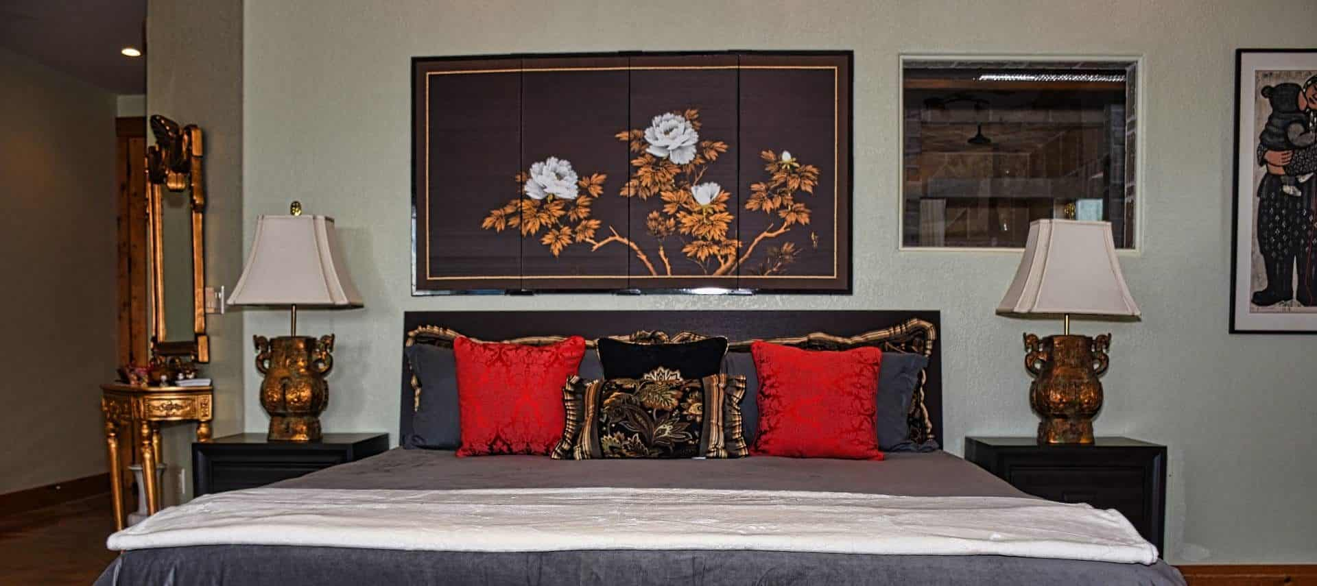 Bedroom with black wooden furniture, dark gray bedding, gray and red pillows, and large artwork hanging on the wall over the bed