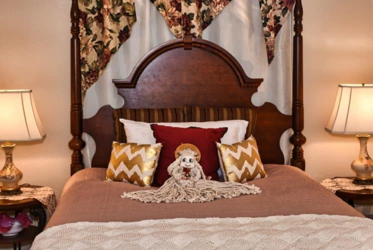 Bedroom with large dark wooden headboard with neutral bedding, white, red, and gold pillows, mop doll, and end tables with lamps