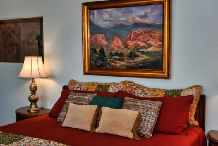 Bedroom with dark wooden furniture, red bedding with multicolored pillows, side tables with ornate lamps, and large painting of a mountain range and rock formations