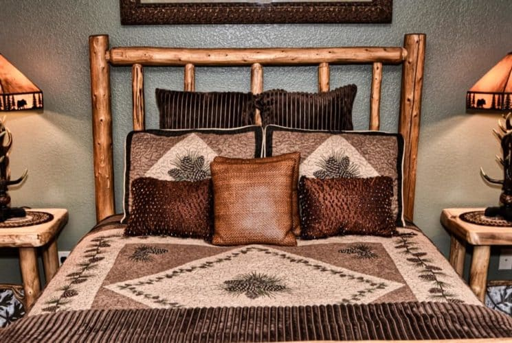 Bedroom with knotty pine bed with brown and gold accent pillows and two end tables with antler lamps