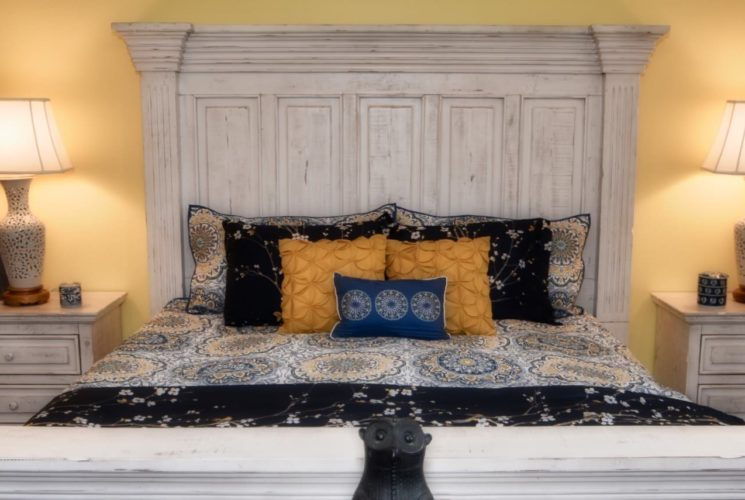 Bedroom with light distressed wooden furniture, black, white, and orange bedding, and side tables with lamps