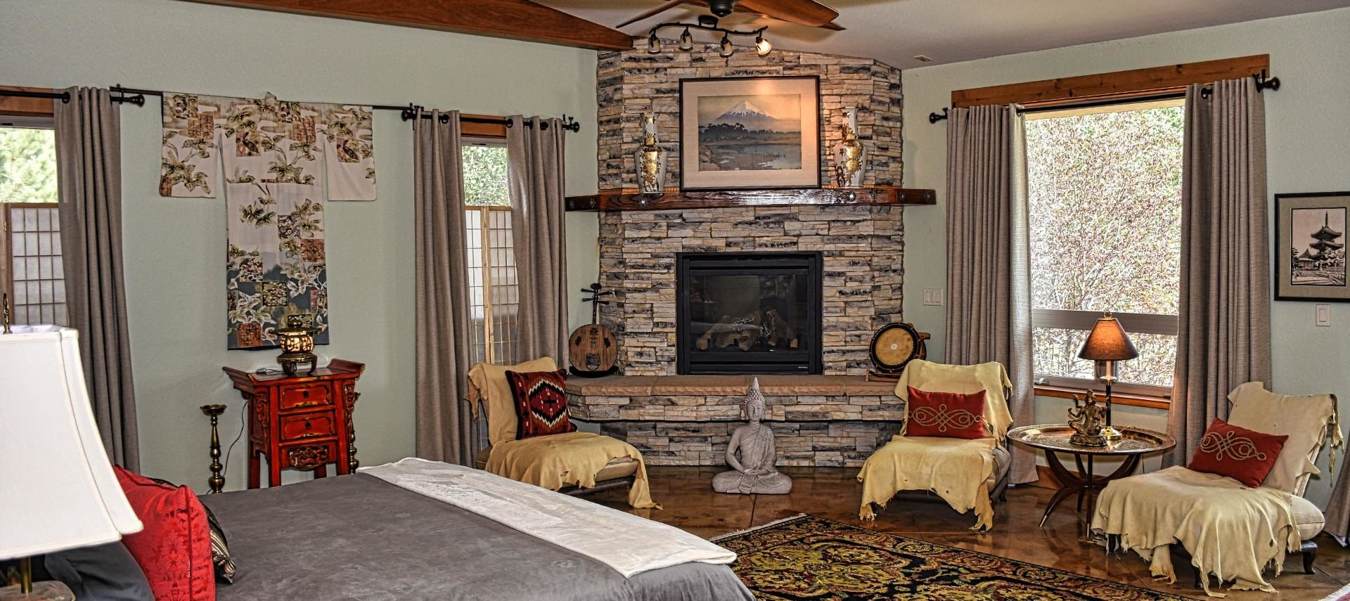 Large suite with bed and gray bedding, stone fireplace, multiple chairs, large area rug, and large windows