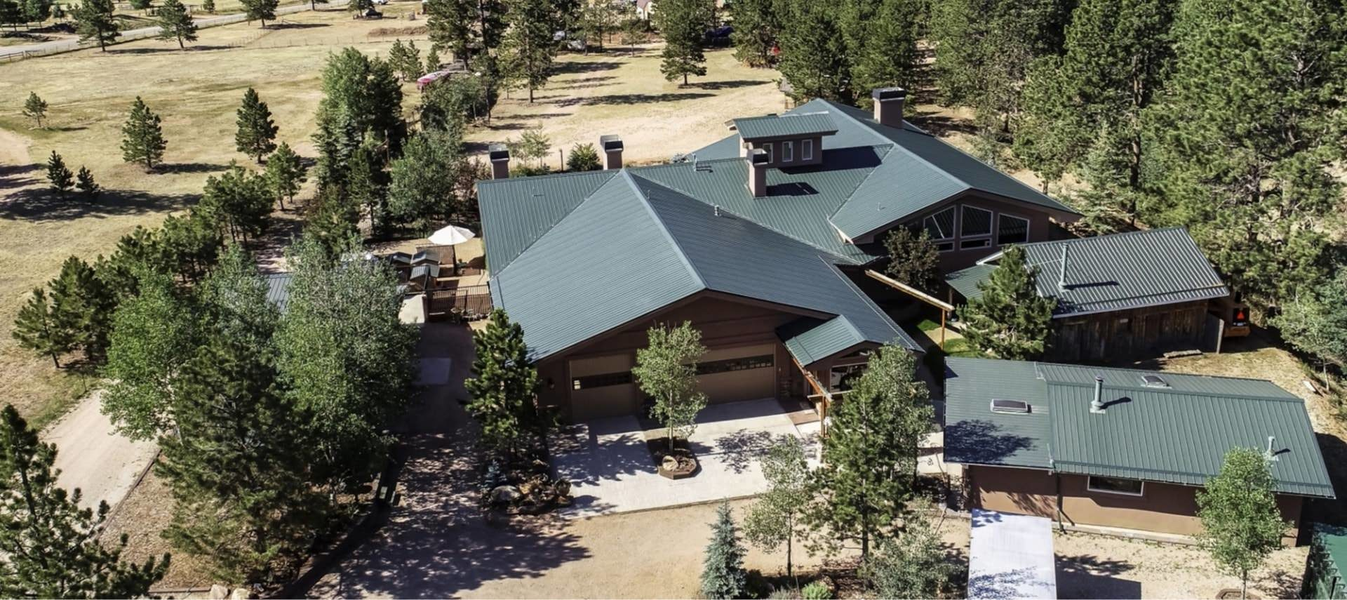 Aerial view of the property with green metal roof and surrounded by large pine trees