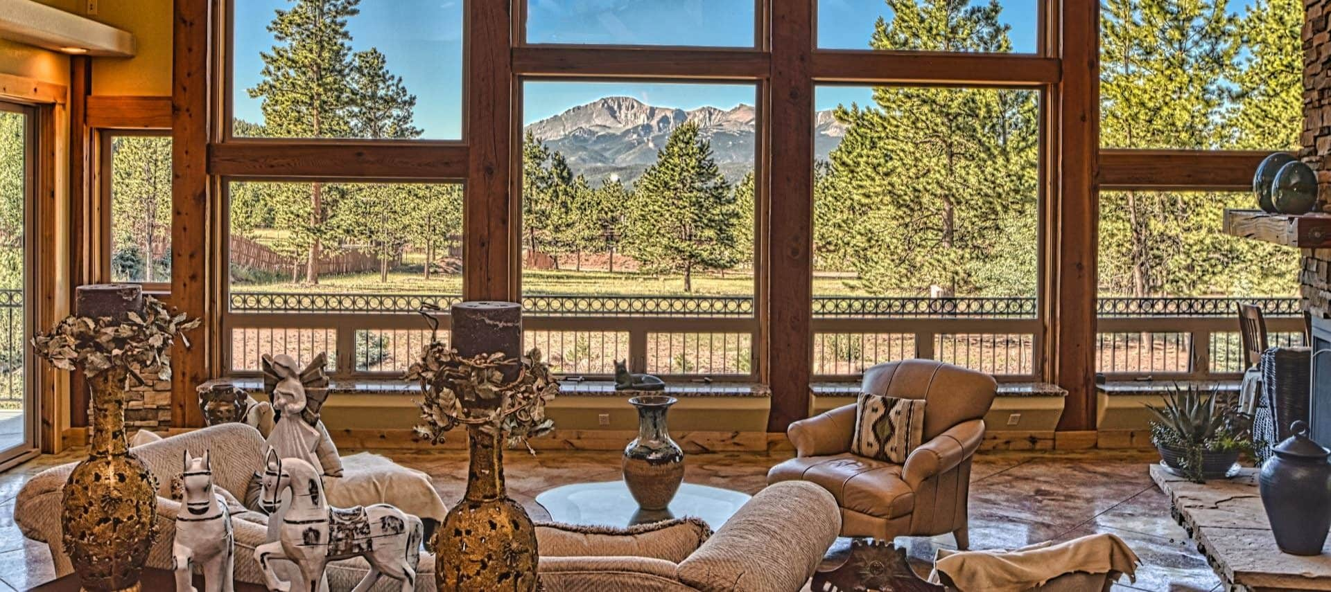 Large great room filled with ornate decorations with a view of large pine trees and mountain range in the background
